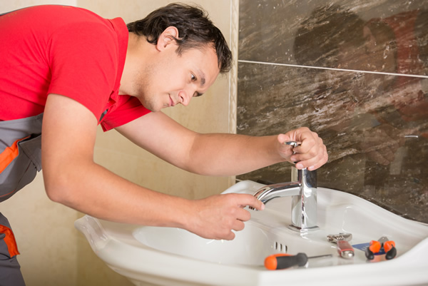 Plumbing contractor working on replacing a bathroom sink faucet